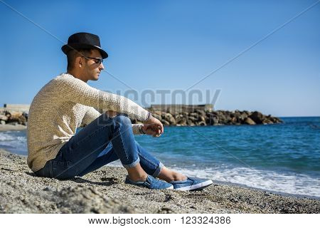 Handsome Athletic Young Man in Trendy Attire, on a Beach in a Sunny Summer Day, Looking Away, against Blue Sky Background.