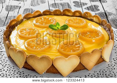 Lemon custard tart decorated with biscuits top view close-up