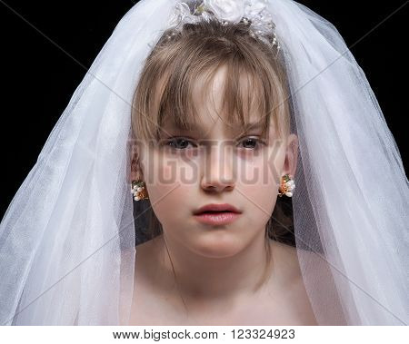 Teen girl - the bride. Portrait of a young, weeping bride. The concept of early marriages with underage children