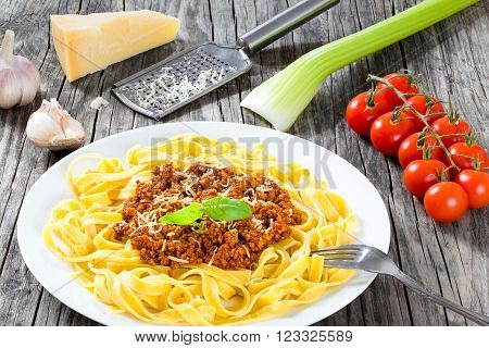 Bolognese ragout with italian pasta on a white plate decorated with basil leaves authentic recipe wooden