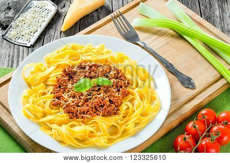 Bolognese ragout with italian pasta on a white plate decorated with basil leaves authentic recipe wooden background with celery garlic cherry tomatoes and parmesan cheese full focus close-up