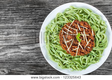 Bolognese ragout with green pasta tagliatelle top view