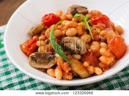 Stewed White Beans With Mushrooms And Tomatoes With Spicy Sauce In A White Bowl
