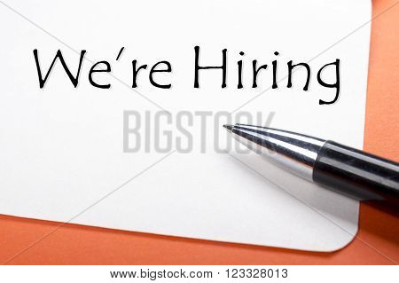 We are hiring. Office desk table with notepad, pen. Top view