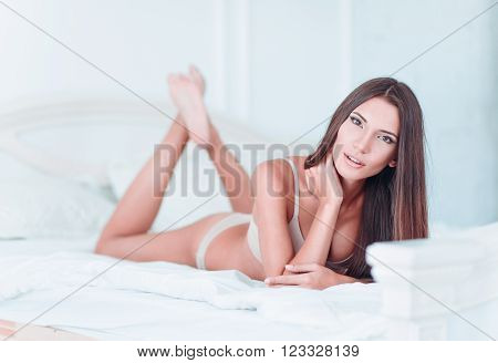 Sexy lovely young girl in lingerie lying on a bed