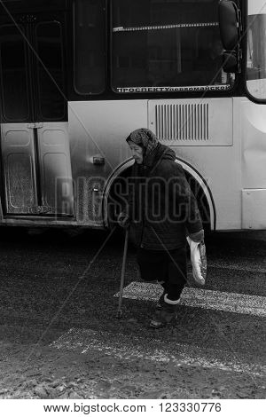 Very Old Woman Crosses A Street With Bus In The Background
