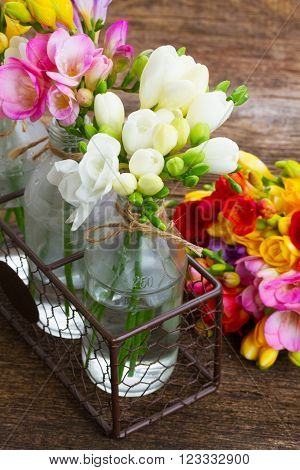 Fresh freesia flowers in vases close up  on wooden table  background