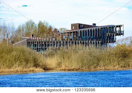 Kristianstad Sweden - March 20 2016: The Vattenriket Naturum building seen from across the river. The river flows in the foreground. Early spring on a sunny day.