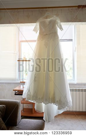 Beautiful wedding dress hanging in the bride's room.