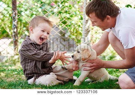 father and son playing with a labrador puppy in the garden.