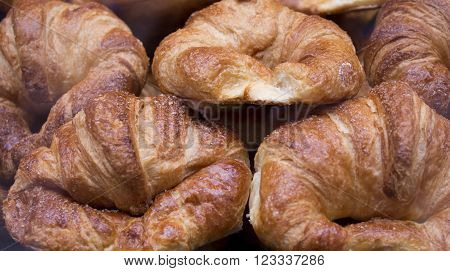 Several stacked croissant. Industrial bakery. Tray with croissant.