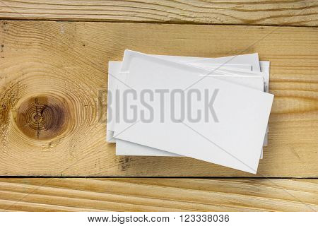 White blank business visit card, gift, ticket, pass, present close up on wooden background. Copy space Blank corporate identity package business card Template for ID