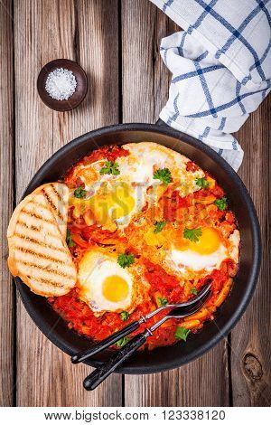 Shakshuka. Fried eggs with tomato paprika and parsley on wooden table
