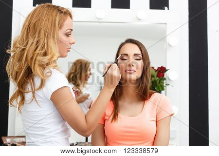 Young woman applying makeup to model in salon