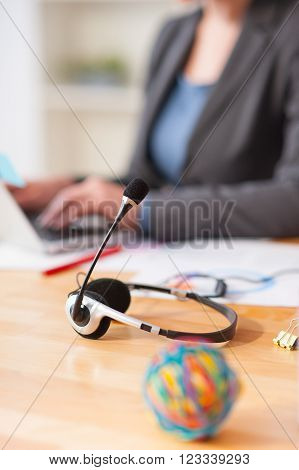 Cheerful female operator is working in call canter. She is sitting at the desk and typing on the laptop. Focus on her headset