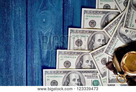 Stack Of Money Dollars Laid Out Like A Ladder With Antique Gold Watch On Blue Retro Stylized Wood Ba