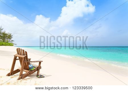 Wooden beach chair with hat and slippers at tropical beach summer holiday concept