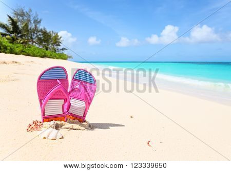 Pink flip-flops on a sunny beach. Tropical beach vacation and travel concept