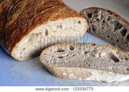 Artisan sourdough white bread loaf sliced on a kitchem chopping board.