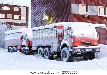 NOVYY URENGOY, RUSSIA - NOVEMBER 19, 2015: Frozen off-road buses KAMAZ 43114 in the street of a polar village.