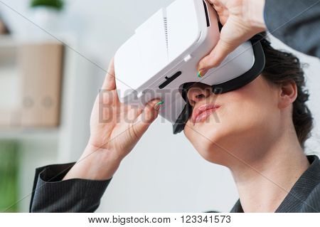 What an interesting film. Cheerful young businesswoman is watching a virtual reality device with interest