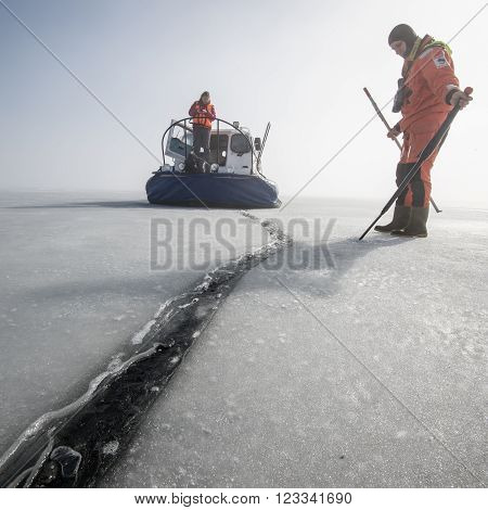 Saint-Petersburg Russia - March 27, 2016: A member of the rescue team checks the thickness of the ice in the Gulf of Finland where the ice fishermen out.