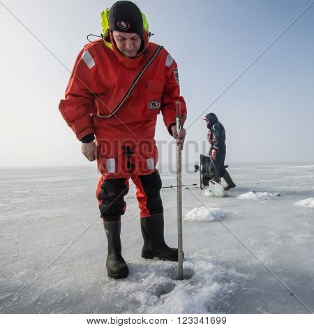 Saint-Petersburg Russia - March 27 2016: A member of the rescue team checks the thickness of the ice in the Gulf of Finland where the ice fishermen out.