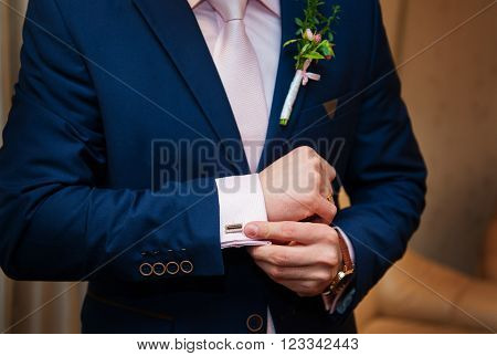 Hands of wedding groom in a white shirt dress cufflinks.