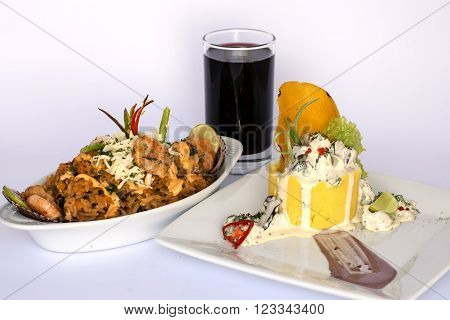 Peruvian Food: Causa Rellena, A smashed popatoes filled with crab meal and Rice with sea food. 2 dishes served as a main meal with a glass of chicha morada (purple  corn juice).
