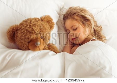 Sweet little girl is sleeping with her teddy bear in bed at home