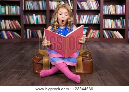 Playful childhood. Little girl having fun at room with bookshelf. Girl reading book and sitting at suitcase