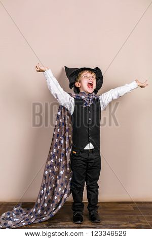 Little boy wearing school uniform and magic cloak with hat. Boy is happy and screaming
