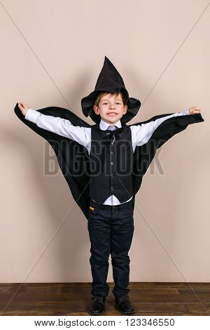 Little boy wearing school uniform and magic cloak with hat. Boy is happy and smiling