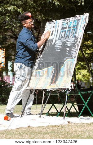 ATLANTA, GA - OCTOBER 7 2015:  A young artist uses his fingers to paint a canvas at the Elevate Art Festival in Atlanta, GA on October 17, 2015.