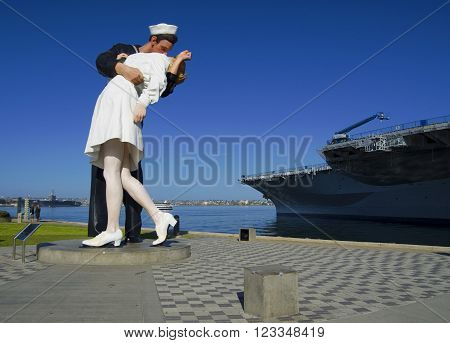 SAN DIEGO, California, USA - March 13, 2016: Kiss statue (Unconditional Surrender) near to aircraft carrier Midway in San Diego harbor USA.
