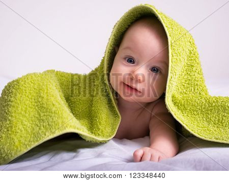 Happy smiled four and a half month old baby girl in a towel after bathing.