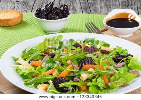 mixed lettuce spinach carrot ham cheese and prunes salad top-view