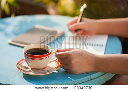 Woman left hand holding coffee cup while writing on notebook at outdoor area in cafe with morning scene