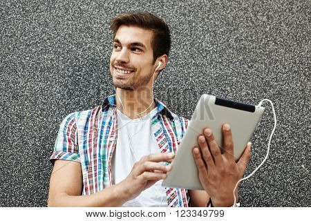 Handsome man enjoying in music via digital tablet