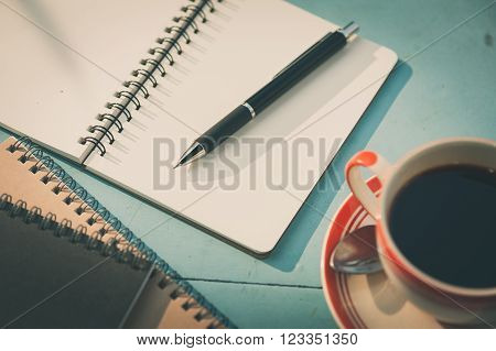 Small notebook and pen beside coffee cup on blue wood table at outdoor area in cafe with morning scene and vintage filter effect