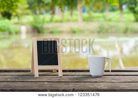 Small A-frame blackboard with blank area for text or message and coffee cup on rustic wood table in morning time