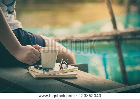 Young woman right hand holding coffee cup above notebokks on wood waterside in morning time on weekend