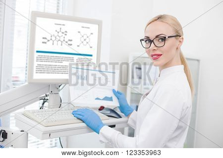 Portrait of cheerful young scientist doing her research in laboratory. She is standing near a computer and typing her report from the paper. The woman is smiling