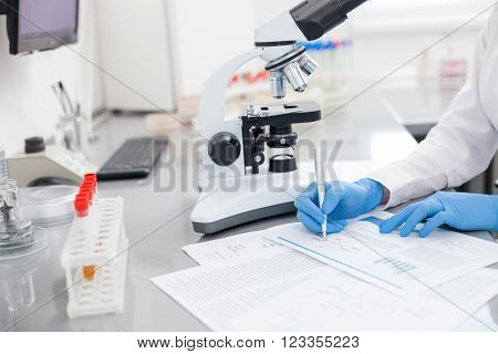 Close up of arms of female scientist writing down the report of her research. She is sitting at the table near microscope and samples in laboratory