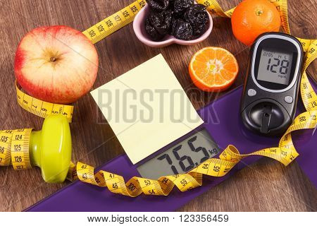 Electronic bathroom scale and glucose meter with result of measurement weight and sugar level, concept of healthy lifestyles, diabetes and slimming, sheet of paper for text