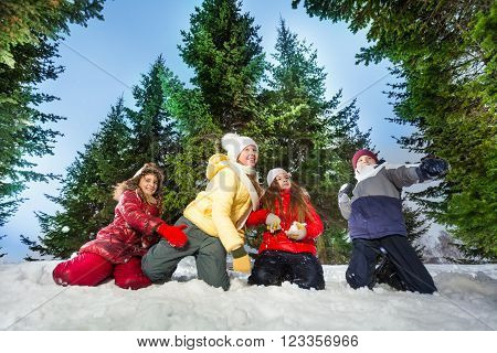 Four kids competes in throwing snowballs, winter games, at snowy winter wood against high spruces
