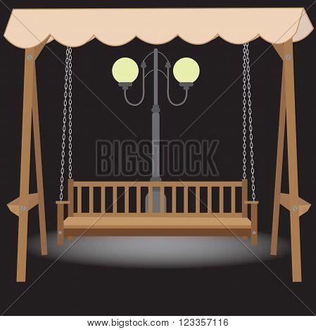 wooden bench swing with a roof made of cloth suspended on chains in the light of the night lamp