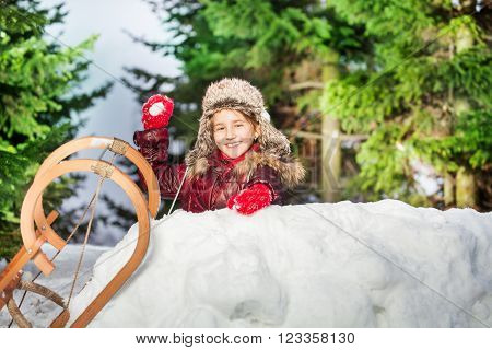 Smiling girl throwing snowball from the snow tower at the sunny winter day