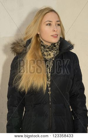 Portrait Of Young Positiv Blonde Caucasian Woman In Black Parka Near The Wall