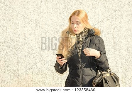 Close Up Portrait Of A Young Fashionable Woman In A Black Parka On The Street Near The Wall Holding